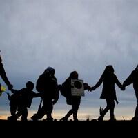 Les silhouettes de personnes marchant main dans la main.