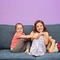 Trois jeunes filles assises sur une causeuse grise regardent la caméra en souriant.