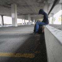 Un jeune adolescent assit la tête baissée, dans un stationnement pour automobile.