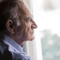 Un homme âgé seul regarde depuis une fenêtre vers l'extérieur