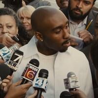Image tirée du film qui raconte la vie de Tupac Shakur, <i>All Eyez on Me</i>. On y voit l'acteur Demetrius Shipp Jr. dans le rôle du rappeur, entouré de journalistes avec leurs micros.