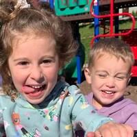 Deux enfants jouant dans un parc sourient à la caméra.