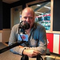 Un homme est assis devant un micro, dans un studio de radio.