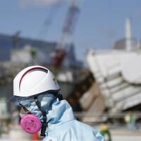 Un employé de la Tokyo Electric Power Company devant les décombres d'un des réacteurs nucléaires à Fukushima