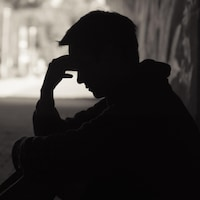 Un homme assis dans une rue sombre se tient le front.