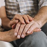 Les mains d'une femme tiennent les mains d'un homme.