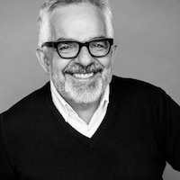 L'architecte Gilles Saucier avec des lunettes et un grand sourire.