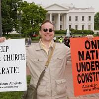 Devant la Maison-Blanche, un homme sourit en tenant deux pancartes en faveur de l'athéisme.