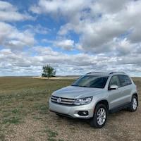 Une voiture stationnée dans les prairies, un arbre en arrière-plan, sous un ciel partiellement nuageux.