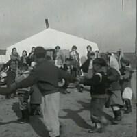 Image en noir et blanc de jeunes Autochtones dansant près d'une tente.