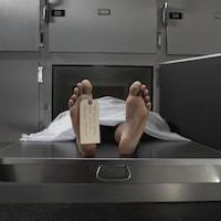 Un corps nu et mort recouvert d'un drap blanc dans un réfrigérateur dans une salle d'autopsie.