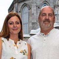 Les deux invités posent à l'extérieur, près d'une église.