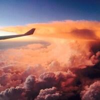 Photo prise à bord d'un avion en vol montrant le reflet orangé du soleil sur les nuages et le bout d'une aile de l'avion.