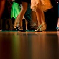 Plusieurs personnes dansent sur un plancher lustré, avec des habits et des chaussures de cérémonie.