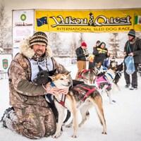Le meneur de chiens, Denis Tremblay, à l'arrivée de la course Yukon Quest en 2019 assis avec deux chiens dans les bras