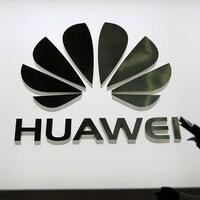 Des personnes marchent devant un panneau lumineux montrant le logo de Huawei.