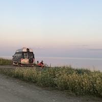 Deux personnes assises au bord de l'eau, à côté d'une roulotte.
