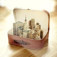 Montage photo des gratte-ciel de New York dans une petite valise vintage.