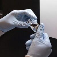 Deux mains gantées tiennent une fiole contenant un liquide transparent.
