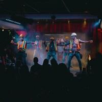 Cinq danseurs sur une scène déguisés en hommes de la construction.