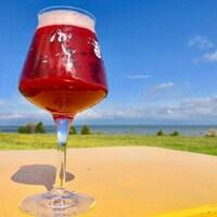 Derrière un verre de bière en gros plan, posé sur une table de la microbrasserie Tête d'allumette, on a une vue imprenable sur le fleuve Saint-Laurent.