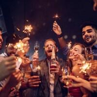 Des jeunes gens trinquent et fêtent avec abandon dans un club de nuit.