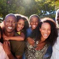 Une famille intergénérationnelle sourit à la caméra par temps ensoleillé.