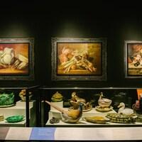 Des plats de service de fantaisie sur un présentoir couvert de verre, surplombé de trois peintures représentant des plats français typiques.