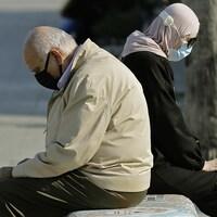 Un homme et une femme assis sur un banc public de la Corniche de Beyrouth tiennent des komboloïs.