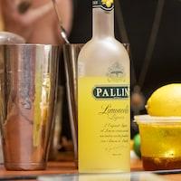 Des bouteilles d'alcool, un citron, un pichet de glace et autres préparations servant à faire des cocktails.