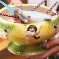 Un grand verre à cocktail de fantaisie orné d'un requin en caoutchouc et de pailles de papier.