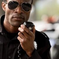 Un policier noir utilise un émetteur radio.