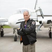 Un homme pose les bras croisé en blouson d'aviateur devant un avion de brousse.