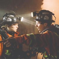 L'actrice et l'acteur sont habillés en tenue de mineur avec une combinaison de protection et se parlent dans une mine.