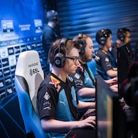 Un athlète de esports est assis devant un écran d'ordinateur lors d'un match du jeu Counter Strike : Global Offensive.