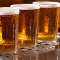 3 verres de bière à côté d'une pompe de bière à pression.