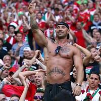 Dans une foule assise, un homme torse nu qui porte un tatouage du mot Hooligan lève le bras gauche.