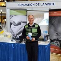 Un homme debout regarde la caméra en souriant devant un kiosque et en tenant une brochure dans ses mains.