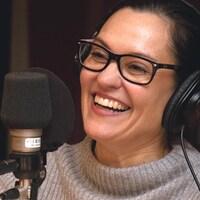 Brigitte Poupart riant dans un studio de radio.