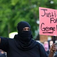 Un homme avec une pancarte brandit le poing en l'air.