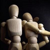 Deux personnages de bois se réconfortent.