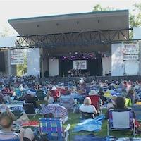 Des gens sont assis sur la pelouse devant une scène au festival folk de Calgary.
