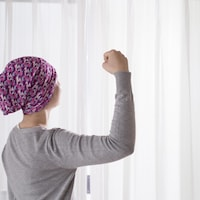 Une femme avec un foulard sur la tête fait un geste de force avec son bras.
