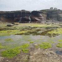 Un ruisseau coule d'une falaise calcaire rouge.