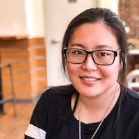 Une jeune femme d'origine asiatique souriante qui porte des lunettes.