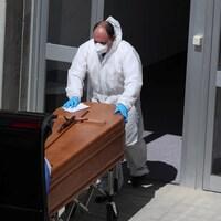 Un homme en tenue de plastique, masqué et muni de gants, pousse un cercueil dans un corbillard.