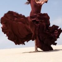Une femme danse sur le sable avec une grande robe.