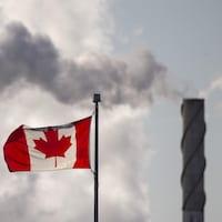 Un drapeau canadien avec, en arrière-plan, de la fumée qui sort d'une cheminée.