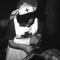 Une infirmière de la Croix-Rouge s'occupe d'un malade dans les années 1950.