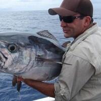 Cyril Chauquet se tient sur un bateau avec un énorme poisson dans les bras.